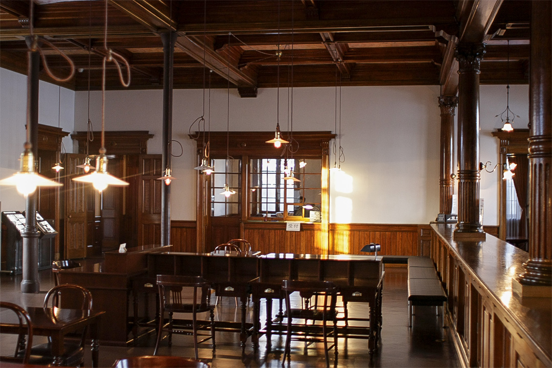 写真:1階営業室。天井から低い位置まで吊り下げられた照明が並ぶ。令和2年7月から令和5年6月まで保存修理工事の為内観、外観ともに非公開。