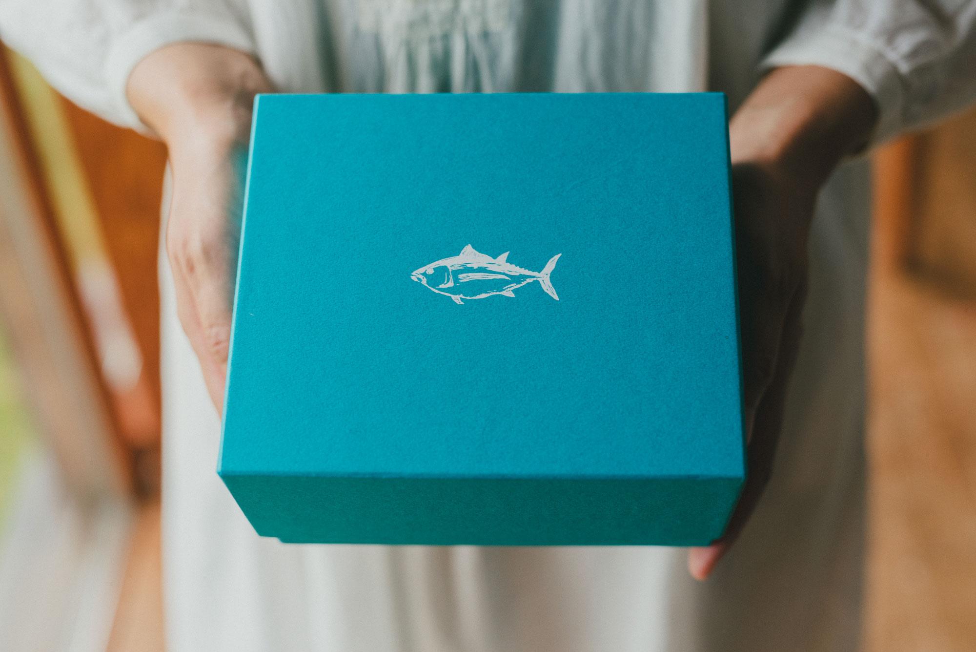 エメラルド色の化粧箱にまぐろロゴがシルバーで箔押しされた、FISHSTANDオリジナルのボックス