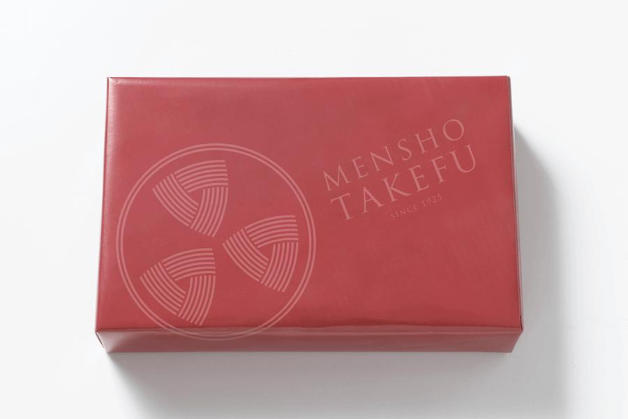 麺匠武生のシンボルマークを大胆にあしらった落ち着いたお色の包装紙でお包みします